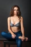 Schönheitsmädchen im BH und Jeans, die auf Lehnsessel siiting sind Stockfoto