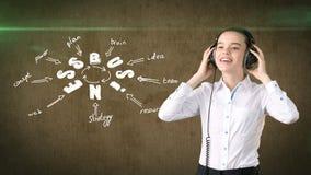 Schönheitsmädchen im Kopfhörer, der die nahe Wand mit einer Geschäftsideenskizze gezeichnet auf sie steht Konzept einer erfolgrei Lizenzfreie Stockbilder