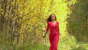 Schönheitsmädchen im roten Kleid mit dem gesunden langen Haar in der Waldglücklichen Frau im Herbst in der Zeitlupe, lächelnd 120 stock footage