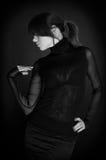 Schönheitsmädchen im schwarzen Kleid über schwarzem Hintergrund Stockbild