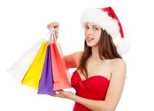 Schönheitsmädchen im Weihnachtshut mit bunten Beuteln Stockfoto