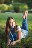 Schönheitsmädchen liegt an Gras sammer Tag Lizenzfreie Stockfotografie