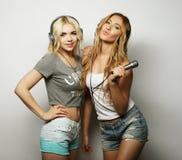 Schönheitsmädchen mit einem Mikrofon singend und tanzend Lizenzfreie Stockfotos