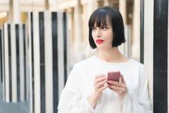 Schönheitsmädchen mit sexy Blick in Paris, Frankreich Frau mit rotem Lippengebrauch auf Smartphone Frau mit Brunettehaar-Griffhan Lizenzfreie Stockfotos
