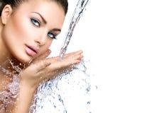 Schönheitsmädchen unter Spritzen des Wassers Stockfoto