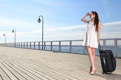 Schönheitsmädchenseeliegeplatzkoffer auf einem Pier Stockfotografie