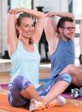 Schönheitsmanngruppe tun Sporteignungstraining in einer Turnhalle lizenzfreie stockfotos
