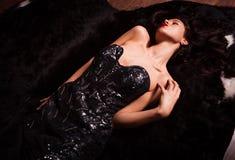 Schönheitsmode Frauen-Porträt Vorbildliche Haltung im Luxuskleid auf schwarzem Pelz lizenzfreie stockbilder
