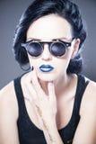 Schönheitsmode-modell-Porträt in der Sonnenbrille mit den blauen Lippen und den Ohrringen Kreative Frisur und bilden Stockfotografie