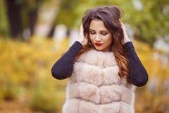Schönheitsmodefrau in der Pelzweste geht in den Park Herbst Stockfotografie