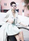 Schönheitsmodell im weißen Kleid, im Pelz und in den hohen Absätzen, welche die blaue Make-upaufstellung im Freien tragen Stockbilder