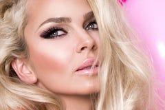 Schönheitsmodell mit dem langen blonden Haar kleidete in einem rosa Kleid an, das auf einem rosa Hintergrund steht Stockbild