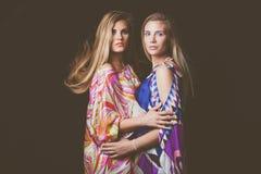 Schönheitsmodeporträt mit zwei blondes jungen Frauen in buntem seidigem Stockfotografie