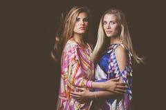 Schönheitsmodeporträt mit zwei blondes jungen Frauen in buntem seidigem Stockbild