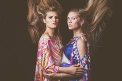 Schönheitsmodeporträt mit zwei blondes jungen Frauen mit dem Haar im moti Stockfotografie