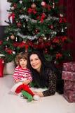Schönheitsmutter und -sohn, die nahe Weihnachtsbaum sitzen Stockbild
