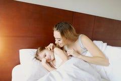 Schönheitsmutter wacht kleine Tochter am weißen Bett mit Sonnenschein auf lizenzfreies stockfoto