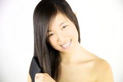 Schönheitsporträt der asiatischen Frau langes Haar bürstend lizenzfreie stockfotografie
