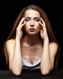 Schönheitsporträt der jungen Frau sitzen am schwarzen Tisch Brunette Stockfoto