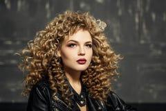 Schönheitsporträt des blonden Mädchens des sexy Kraushaars in der schwarzen Lederjacke Studio mit dunklem Hintergrund lizenzfreie stockbilder