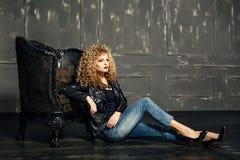 Schönheitsporträt des blonden Mädchens des sexy Kraushaars sitzen auf dem Boden, der auf dem Stuhl sich lehnt Studio mit dunklem  lizenzfreie stockfotos