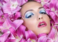 Schönheitsporträt des hübschen europäischen Mädchens in den Lilien blüht Stockbilder