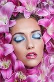 Schönheitsporträt des hübschen europäischen Mädchens in den Lilien blüht Lizenzfreies Stockbild