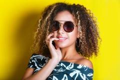 Schönheitsporträt des jungen Afroamerikanermädchens mit Afrofrisur Mädchen, das auf dem gelben Hintergrund, Kamera betrachtend au lizenzfreie stockbilder