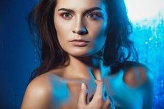 Schönheitsporträt des schönen weiblichen Modells auf einem blauen Hintergrund Stockbilder