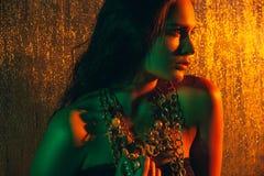 Schönheitsporträt des schönen weiblichen Modells auf einem orange Hintergrund Stockbild