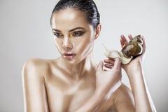 Schönheitsporträt einer jungen Frau, die Schnecke hält Stockfotografie