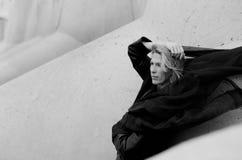 Schönheitsporträt, fliegender schwarzer Schal und blondes langes Haar, Betonblockhintergrund im Seehafen Stockbild
