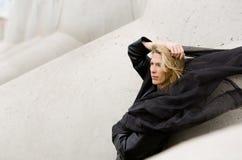 Schönheitsporträt, fliegender schwarzer Schal und blondes langes Haar, Betonblockhintergrund im Seehafen Lizenzfreies Stockbild