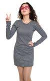 Schönheitsporträt-Showsiegeszeichen des jungen Mädchens, kariertes Schwarzweiss-Kleid, rosa Sonnenbrille im Herzen formen, langes Stockfotos