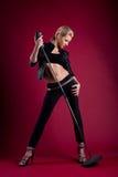 Schönheitssänger im schwarzen Leder auf Rot mit mic Lizenzfreies Stockfoto