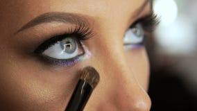 Schönheitssaalmaskenbildner verursacht Wimpern mit einem blonden Kajalstift der Bürstewimperntusche stock footage
