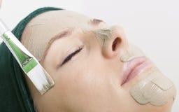 Schönheitssalon. Kosmetiker, der Gesichtsmaske am Frauengesicht anwendet. Lizenzfreies Stockfoto
