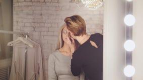 Schönheitssalon - Maskenbildner und blonder vorbildlicher naher Spiegel in der Umkleidekabine Stockfotografie