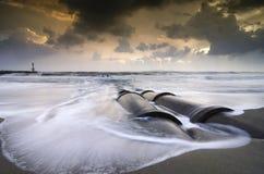Schönheitssonnenaufgangsonnenuntergang auf dem Strand mit weichen Wellen konkreter Entwässerungsabzugskanal und -leuchtturm Stockbild