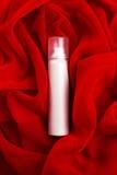 Schönheitsspray (Aerosol) über rotem Stoffhintergrund Stockbild
