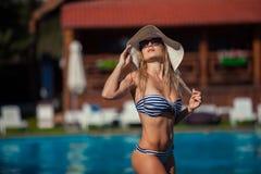 SchönheitsSwimmingpool-Sommerferien summertiA schöne junge Frau in der Badebekleidung am Poolside steht Lizenzfreies Stockbild