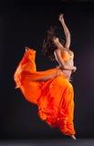 Schönheitstänzer springen in orange Schleier - arabische Art Lizenzfreies Stockfoto