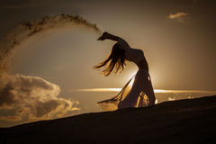 Schönheitstanzen bei Goldsonnenuntergang Stockbild