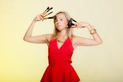 Schönheitsverfahren, Frau hält Make-upbürsten nahe Gesicht. Lizenzfreie Stockbilder