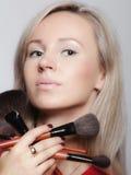 Schönheitsverfahren, Frau hält Make-upbürsten nahe Gesicht lizenzfreie stockbilder