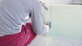 Schönheitszeitlupe im Bau und in der Reparatur - Gips-Nut und Feder-Blöcke des männlichen Erbauers sägende stock video footage