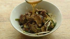 Schöpflöffel, der braune Suppe auf gedünstetem Schweinefleisch und Sojabohnensprosse in der Schüssel pouping ist stock footage