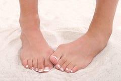 Schüchterne Füße mit Pedicure, das im Sand steht Stockfoto