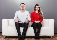 Schüchterne Frau und Mann, die auf Sofa sitzt Erstes Datum