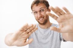Schüchterne Hasse des Manngefühls, die Hände in Richtung zur Kamera ziehend, um Gesicht von der Taschenlampe zu bedecken machend  lizenzfreie stockfotos